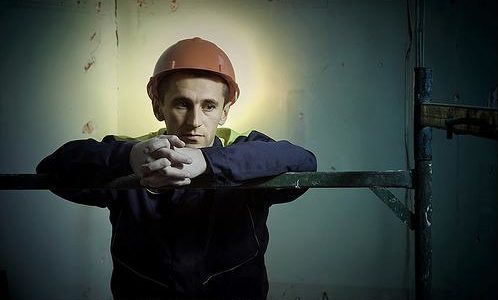 Pensive construction worker with halo of light