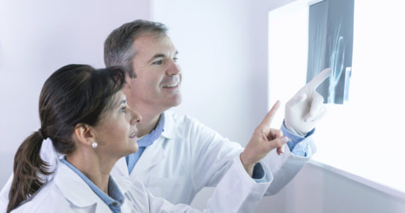 Doctors at the hospital looking at a hand x-ray - medical exam concepts
