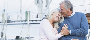 An affectionate, mature couple at a marina standing together on a dock, luxury boats and yachts in the background. The senior man is holding his wife's hand, and she is resting her head on his shoulder, smiling.