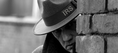 Film Noir style gangster/detective hiding behind a brick wall
