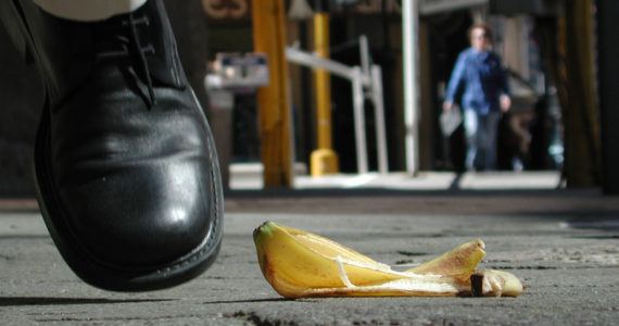 Man nearly steps on a banana peel on a city street.