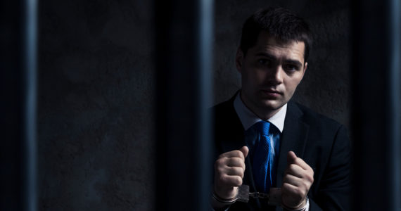 Businessman in prison. Financial crime concept.