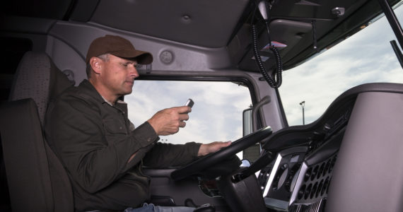 A truck driver texts while behind the wheel