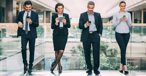 Mature businessman with his younger team using smart phones and digital tablet inside modern office building.
