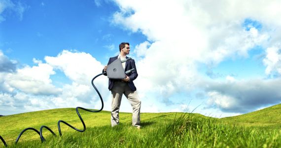 Concept of electricity. Man is pulling a large power plug with a cable though some green hills.